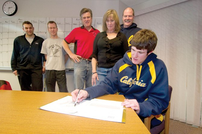Steamboat Springs quarterback Austin Hinder signs his letter of intent to play with the University of California, Berkeley, on Wednesday afternoon at Steamboat Springs High School. Hinder helped lead the Sailors to the state finals as a senior. He was joined by, from right, his parents, Bill and Kathy, and coaches Aaron Finch, Lonn Clementson and David May.  