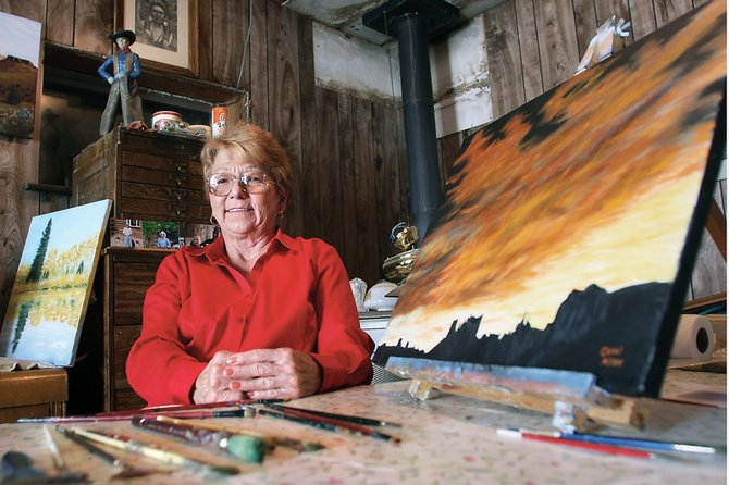 Carol Allen sits at her workspace in front of a painting Thursday in her home. Allen will feature the piece, along with a few other paintings she recently finished, during Saturday's 15th annual Art Walk.