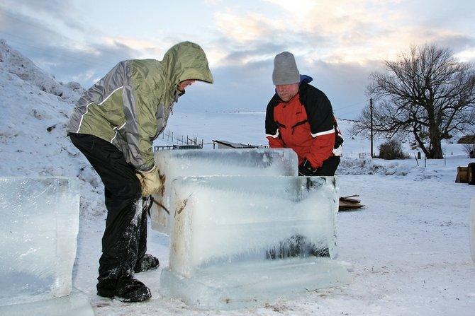 Buddy Cassaday, left, and Michael Campe hoist a 300-pound block of ice Thursday in the beginning stages of what will be an ice castle at the Wyman Museum. The castle will lead to a tubing area for children to play.