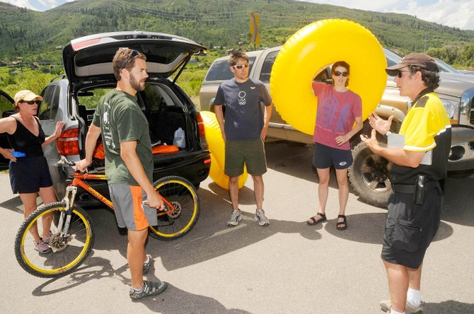 Steamboat Springs Community Service Officer Scott Schaffer explains the rules of the Yampa River to tubers, from left, Barbara Shortle, Alex Shortle, Mario Russo and Margaret Shortle in July 2009 at the Rotary Park parking area.