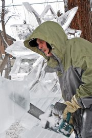Buddy Cassaday cuts through a 300-pound block of ice with a chainsaw specially tuned and sharpened for his trade Friday at Alice Pleasant Park. Cassady starting sculpting ice in 1982 and has worked with Michael Campe since 1985 as a chef and sculptor.