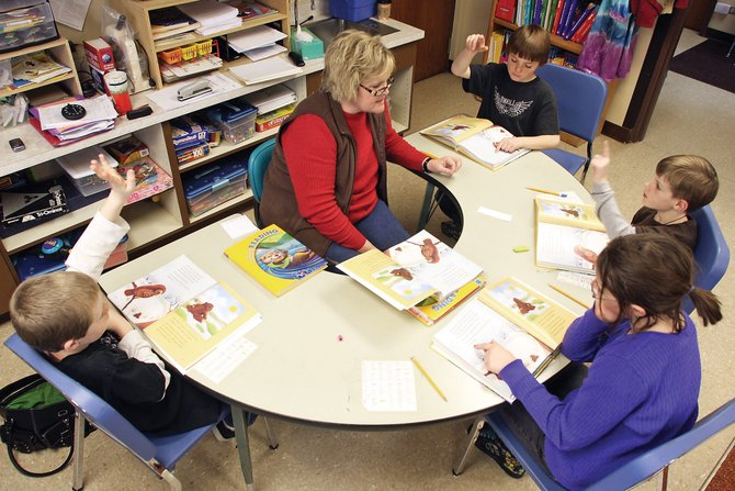 Teacher Rhonda Willingham leads a reading group Wednesday morning with her students at Maybell Elementary School. With the help of paraprofessionals, Willingham teaches 14 children in the one-classroom school.