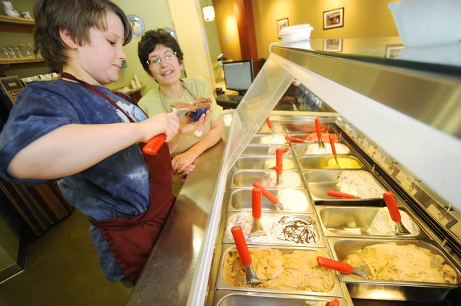 Ciao Gelato owner Lynne Romeo watches Lowell Whiteman Primary School fifth-grader Wyatt Gray dish gelato Tuesday at the downtown store. Wyatt was working at the store for the school's mentoring day.