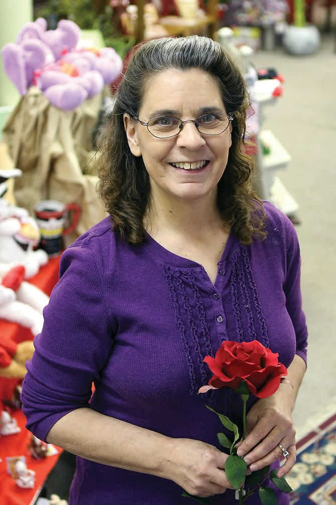 Mary Bouchard holds a synthetic perfect rose Friday at The Flower Mine, 410 W. Victory Way. Bouchard has worked at the floral shop for more than a year. She said she enjoys the job because of the customers she encounters.