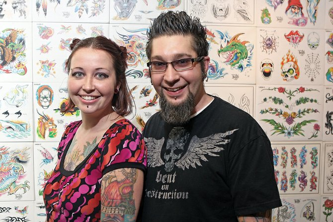Carrie and Jimmy Clark stand in front of a flash art display wall in their tattoo parlor, Liquid Flesh Tattoo, on Yampa Avenue. The Clarks reopened the shop at the new location Feb. 12, after closing a parlor operated out of Bad Axe Custom Cycles more than a year ago.