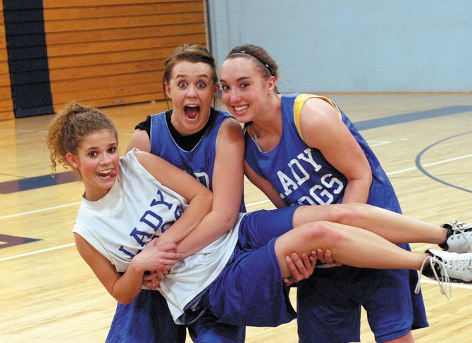 Moffat County High School seniors Lindsey Yoast, left, and Jessi Moser, right, hold up fellow senior Amanda Snyder on the eve of the MCHS girls varsity basketball team's first-round playoff game against John F. Kennedy High School. The team will play at 6:30 p.m. today at the MCHS gymnasium, 900 Finley Lane.