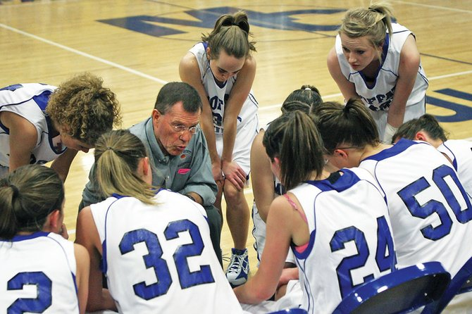 Moffat County High School girls varsity basketball coach Craig Mortensen goes over the game plan during a timeout in the fourth quarter of the state playoff opener against John F. Kennedy High School.