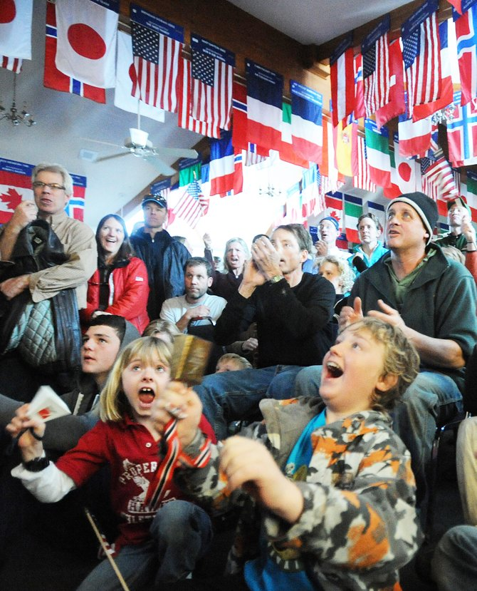 Madison Knutson, 7, left, and Bastion Elkins, 10, right, lead the cheers at Olympian Hall in Steamboat Springs as Billy Demong skates the final leg of the team Nordic combined relay event at the Olympics in Vancouver, British Columbia. About 200 people in the hall watched live broadcasts of the race on TV.