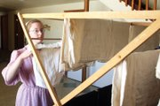 Lori Yoder, 17, hangs laundry on a rack downstairs in her familys home. The Yoder family rotate household chores among the 11 children. 