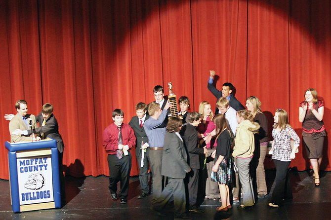 The Moffat County High School Speech and Debate Team celebrates with the district sweepstakes trophy Saturday at the Moffat County High School auditorium. The trophy is awarded to the team sending the most members to the state tournament. MCHS had 13 students qualify and won the trophy for the third year in a row.