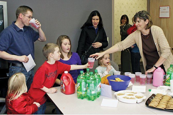 Sue Birch, chief executive officer of the Northwest Colorado Visiting Nurse Association, right, hands a cup to Seth White, 6, during an open house to celebrate Cole White, far left, moving on to a new position in Kremmling. White served almost three years as the organization's director of operations and will use his accounting background as a chief financial officer at the Kremmling Memorial Hospital.
