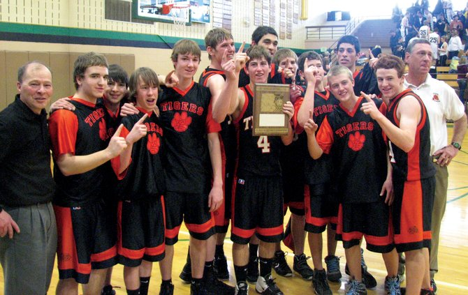 The Hayden High School boys basketball team celebrates its district championship win against Meeker on Saturday in Rangely.