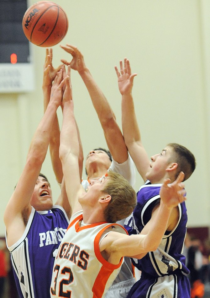 Hayden's Murphy Smartt, No. 32, and Rene Valdez, back, leap against a pair of John Mall players for a rebound Saturday as the Tigers beat the Panthers in the regional championship game.