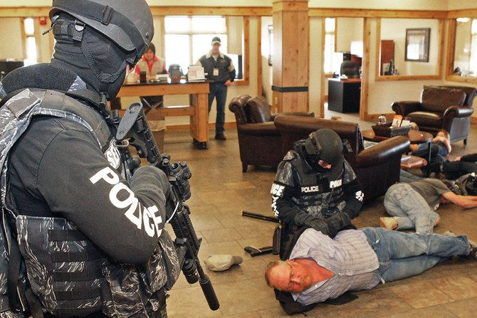 A member of the Special Response Team handcuffs Doug Vaughan while another team member keeps watch during a simulation exercise Saturday at Yampa Valley Bank in Craig. Vaughan played the role of a gunman who barged into the bank and took hostages during the mock drill.