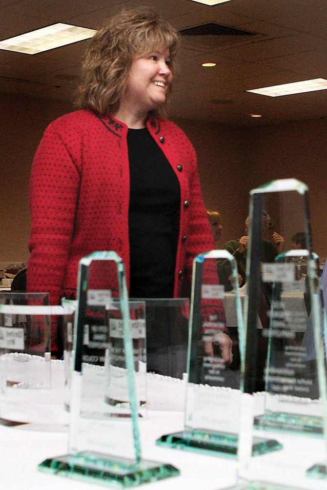 Corrie Ponikvar, executive director of Moffat County United Way, walks by the award display during a luncheon to recognize the agency's donors Tuesday at the Holiday Inn of Craig. The Moffat County United Way raised more than $515,000 in its 2010 campaign.