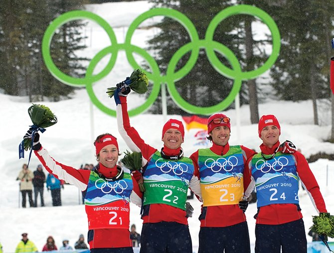 The members of the silver-medal winning U.S. Nordic Combined Ski Team, shown celebrating Feb. 23 during the flower ceremony at Whistler Olympic Park in Whistler, British Columbia, will go abroad to meet with U.S. troops next month. From left are Brett Camerota, Todd Lodwick, Johnny Spillane and Billy Demong.