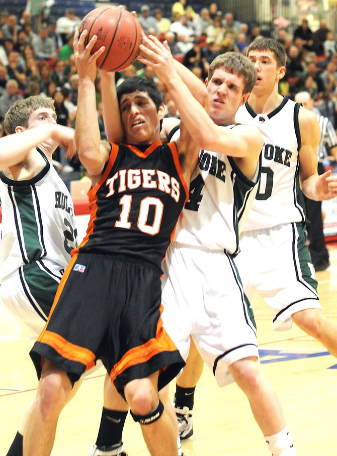 Hayden's Rene Valdez tries to haul down a rebound in the face of Holyoke defenders Thursday during the first round of the Class 2A boys basketball tournament in Pueblo. The Tigers lost the game, 50-36.