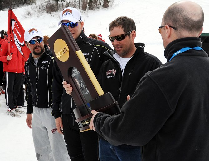University of Denver skiing coach Andy LeRoy accepts the NCAA championship trophy Saturday in Steamboat Springs.