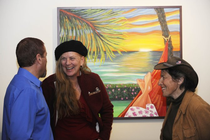 Writer Harriet Freiberger, right, and painter Carol Jean visit with Darrel Levingston in front of one of Jean's paintings Friday during the Steamboat Springs Arts Council's annual meeting at the Depot Art Center.