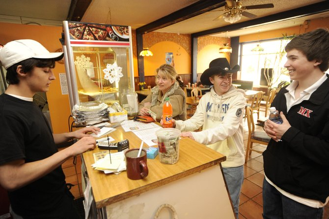 Wolf Mountain Pizza employee Chris Skof, left, rings up orders placed by, from right, John Henry Ronan, of Massachusetts, and Steamboat Springs residents Jonathan and Laurie Milne on Saturday at the downtown Hayden business.  The town has collected $205,392 in sales tax from January through March, down nearly 12 percent from 2009.
