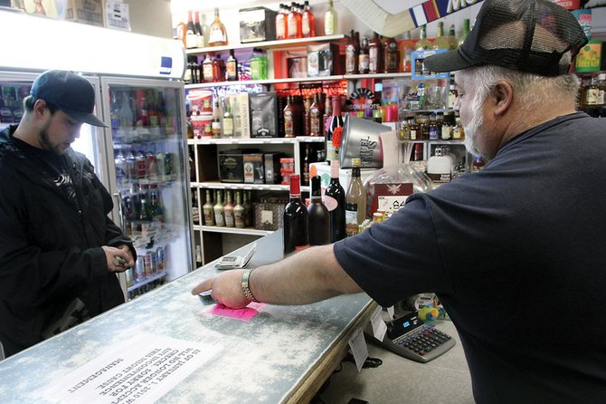 Tim Alexander, right, gives Casey Doolin, 28, his driver's license back after checking his age before selling him a couple of bottles of wine Saturday at Stockmen's Liquors on Pershing Street in Craig. All of Craig's 13 liquor and convenience stores passed last week's compliance check.