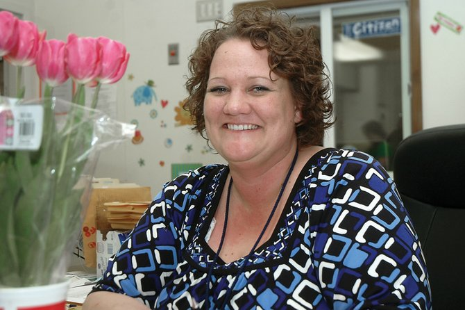 Rachel Jensen sits at her desk at Sandrock Elementary School, where she works as a secretary. Once a social worker for hospice patients, Rachel and her husband, Travis, and their three sons have lived in Craig for four years.