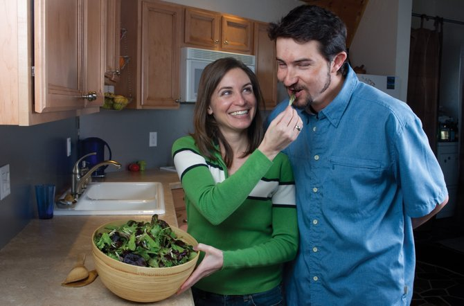 Christina Yeager and her husband, Chad, enjoy some lettuce in the kitchen of their Steamboat Springs home. The couple owns Firefly Mountain Produce, which offers naturally grown salad and braising greens, as well as some root crops and herbs.