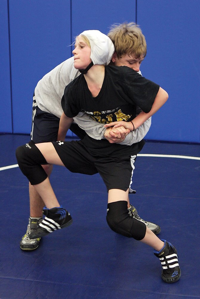 Ashlee Griffiths, front, grapples with Moffat County High School freshman Garrett Stewart during a practice at Craig Middle School. Griffiths, a seventh-grader at CMS, hopes to become the first girl to be on the MCHS squad.
