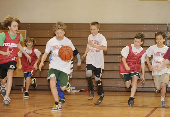 Tyler Johnson, middle, has adapted to life after losing both his feet to meningitis in June 2008. Prosthetic legs allow him to run and keep up with his sixth-grade classmates at Steamboat Springs Middle School.