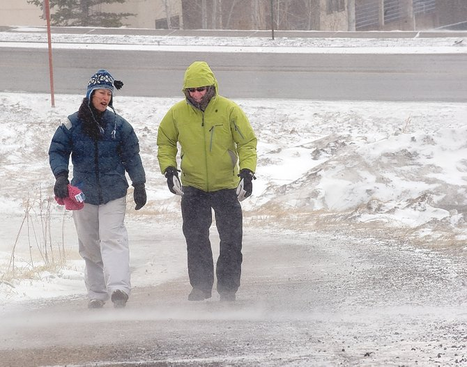 Jennifer Smith, left, and Tommy Smith battle high winds and blowing snow while walking from the base of the ski area to the Knoll Parking Lot on Friday. The gusty wind forced the gondola and chairlifts to close for the day.