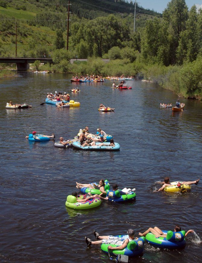 "Tubers float down the Yampa River during summer 2009. The group of rafters got in near Walton Pond and floated through downtown Steamboat Springs. Colorado House Bill 1188, which sought to settle the state's ""right to float"" laws, was put on hold rather than voted into law in the state Senate on Friday."