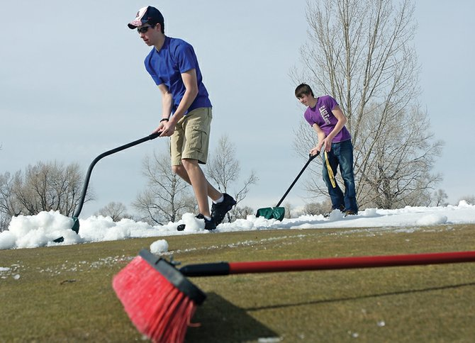 Parker King, left, and Mark Dockstader work to clear snow away from the sixth green Thursday at Yampa Valley Golf Course. The two are Moffat County High School golf team members who volunteered time during their spring break to the golf course.
