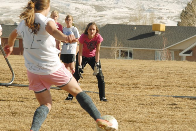 Goalie Jaycee McCoy, center, prepares to deflect a shot from Justine Hathhorn, left, on Monday at Moffat County High School. The MCHS girls varsity soccer team will play at 4 p.m. today in Palisade. The MCHS girls junior varsity team will play at 5:45 p.m. today, also in Palisade. For more, see page 13 in sports.