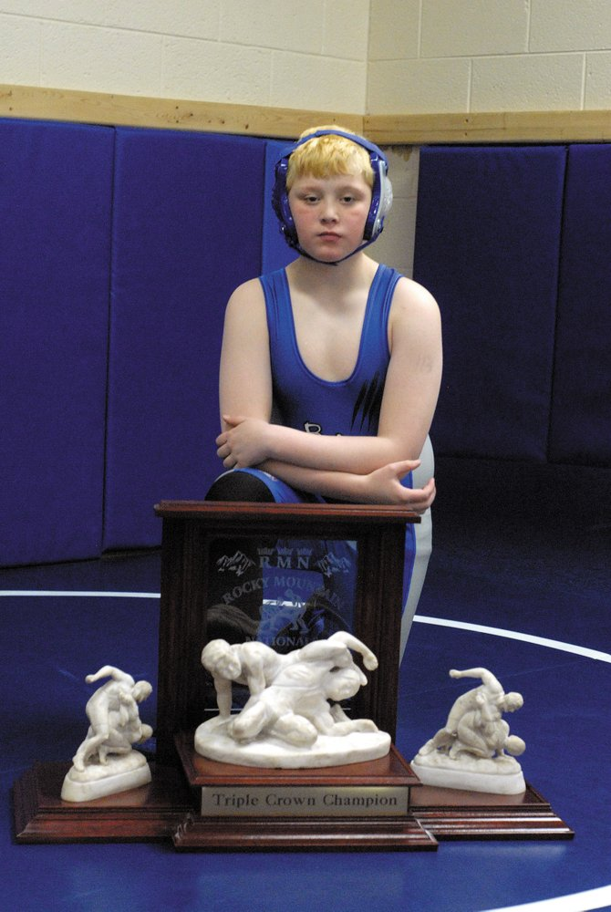 Deven Mosman, 10, stands behind his Triple Crown trophy Monday at Moffat County High School. Mosman became the first Craig Bad Dogs wrestler to win the Triple Crown, a feat that includes winning three national tournaments.