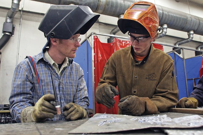 Curtis Ellgen, right, a Moffat County High School senior, gives Tyler Jacox, a property technician for the Colorado Division of Wildlife, some tips on welding Tuesday in the MCHS agriculture and metal working building. The welding seminar was part of a DOW property technician's annual conference, which took place in Craig on Tuesday and Wednesday.
