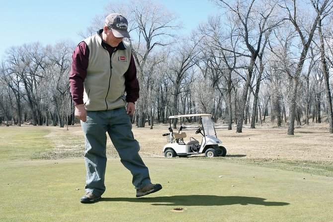 Tim Boyle, Yampa Valley Golf Course superintendent, looks at the green around the cup Tuesday on the second hole. Boyle said the golf course's greens are in good shape this year after the winter.