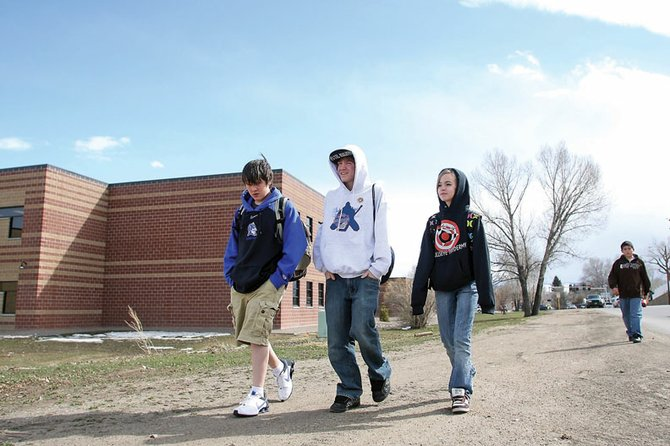 Craig Middle School students Kaleb Albert, from left, Cade Bangs and Mariah Bangs walk along a dirt path alongside the west side of the school on Yampa Avenue on Wednesday afternoon. The city of Craig worked with the Moffat County School District to acquire $188,905 in grant funds from the Colorado Department of Transportation to provide safe sidewalk routes for CMS and Sandrock Elementary School students.