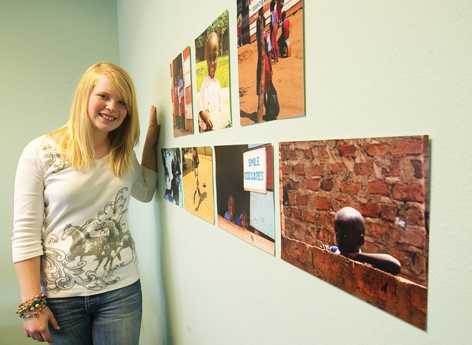Mackenzie Holmberg is raising money to buy a cow for the Come, Let's Dance orphanage in Uganda, which is shown in a photographic display by Tracie Patterson that is hanging on the wall of the Christian Heritage School's office. Mackenzie is planning to visit the orphanage this month.