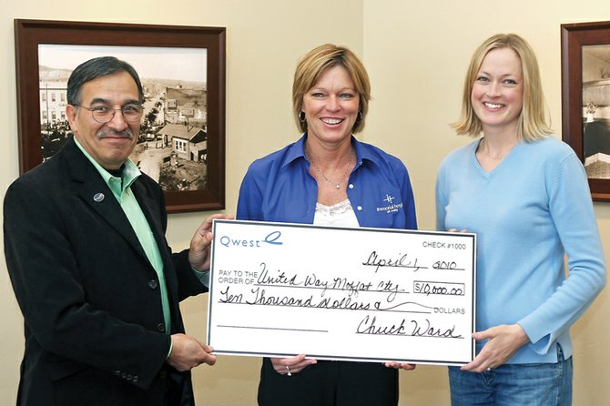 Abel Chavez, from left, Colorado markets manager for Qwest Communications, hands a $10,000 check Thursday to Moffat County United Way board members Amy Knights and Michelle Tucker. United Way raised $515,000 for Moffat County human service agencies, exceeding its goal of $485,000.