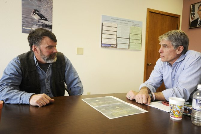 U.S. Sen. Mark Udall, D-Colo., right, meets with district forester John Twitchell on Friday at the Colorado State Forest Service office to talk about logging operations related to the pine beetle epidemic.