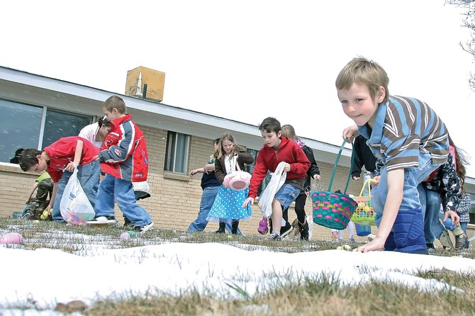 Dalton Sherwood, 7, far right, reaches for an Easter egg during an Easter Sunday hunt at Sandrock Ridge Care & Rehab. About 100 children scampered around the grounds, filling their baskets with plastic, colored eggs.