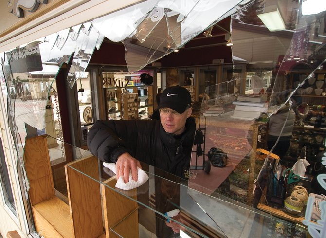Larry Stroman, owner of The Silver Lining Jewelry, Beads & Charms, cleans up broken glass after someone broke several windows at the Torian Plum Plaza business and made off with an undisclosed amount of jewelry and gems in an apparent burglary.