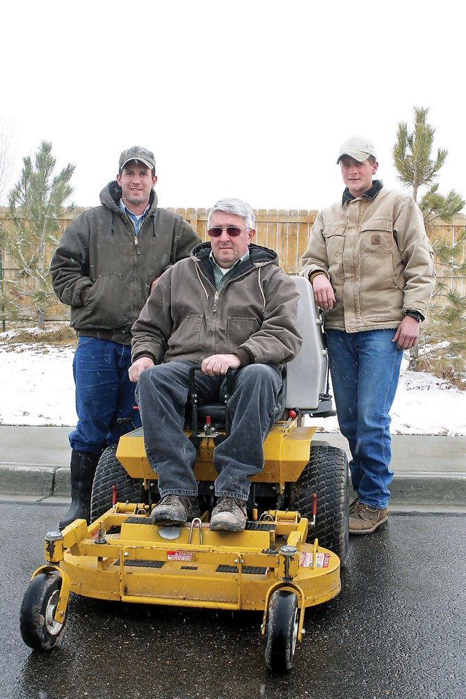Ron Weaver, owner of C&K Lawn Care, sits in the driver seat of a riding lawn mower with his son-in-law, Durrell Martin, left, and his son, Josh Weaver, on Tuesday in the Walmart parking lot. C&K Lawn Care was recently awarded a contract to mow parts of Moffat County's grounds.