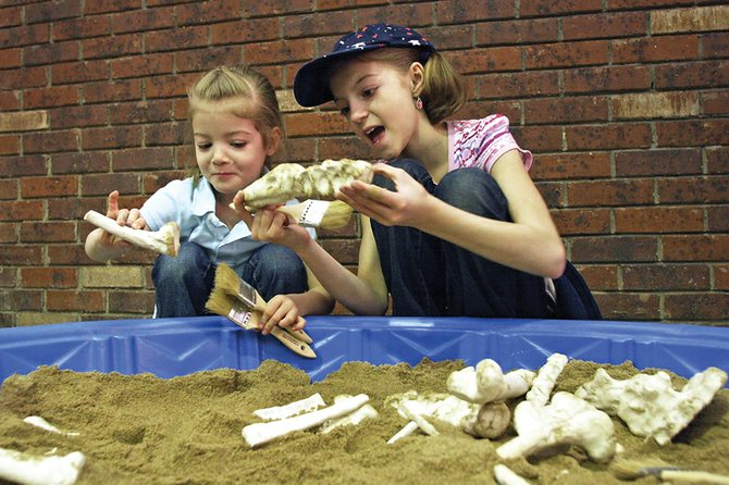 Carmen Bolton, 3, left, and her sister, Laura, 9, look at replicated dinosaur bones Saturday in a sandbox provided by Calvary Baptist Church during the 2010 Celebrate Children Festival at Centennial Mall.
