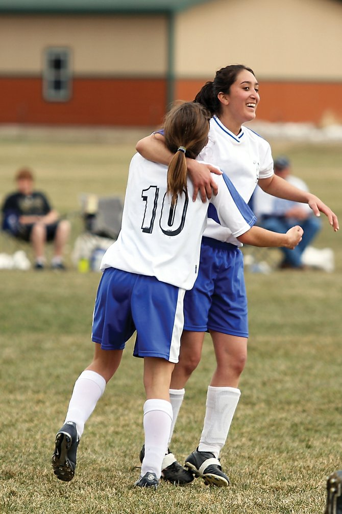 Kelly Ciesco, left, is congratulated by Lili Torres after Ciesco scored the fifth goal against visiting Roaring Fork High School on Saturday. The Moffat County High School girls varsity soccer team won, 6-0.