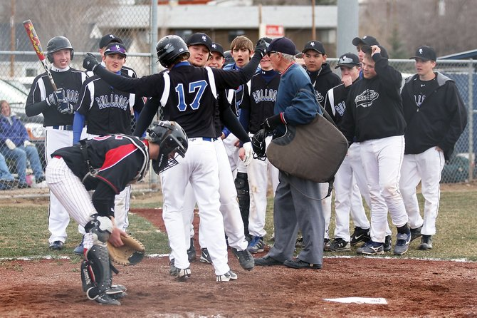 Austin Sadvar, No. 17, a Moffat County High School senior, chest bumps Halen Raymond after Sadvar hit his first home run of the season Tuesday against visiting Steamboat Springs High School at Craig Middle School. The Bulldogs went on the win their home opener, 15-7.