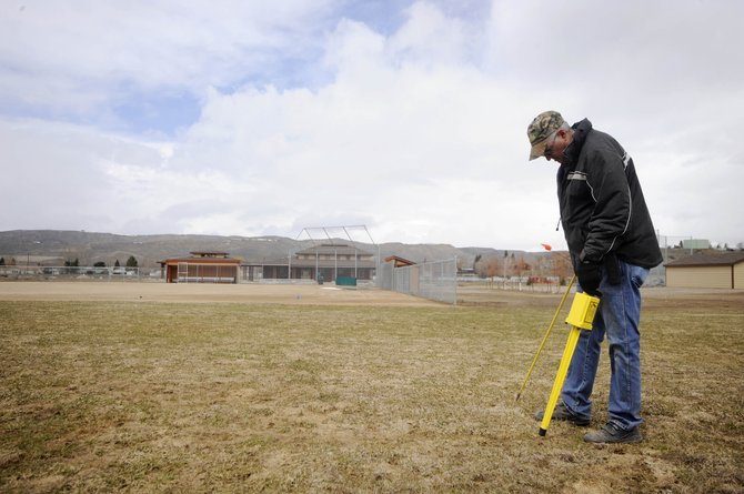 Hayden Public Works employee Ron Cless locates sprinkler heads Tuesday at one of three new baseball fields built at Dry Creek Park. The town is preparing the fields for use this summer.