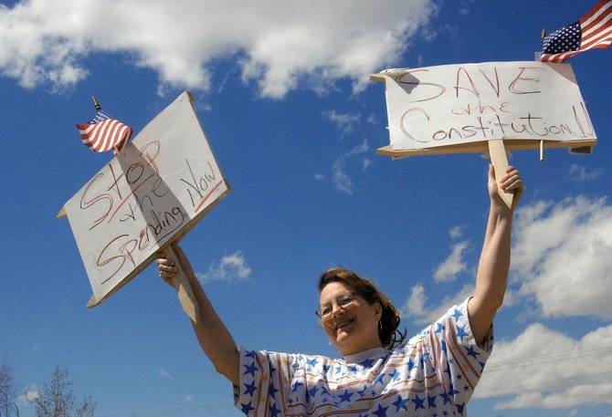 Lynne Herring, of Craig, holds signs during last year's Tax Day Tea Party protest in front of the Moffat County Courthouse. This year, the Moffat County tea party will host another protest from 5 to 6 p.m. Thursday at the courthouse.