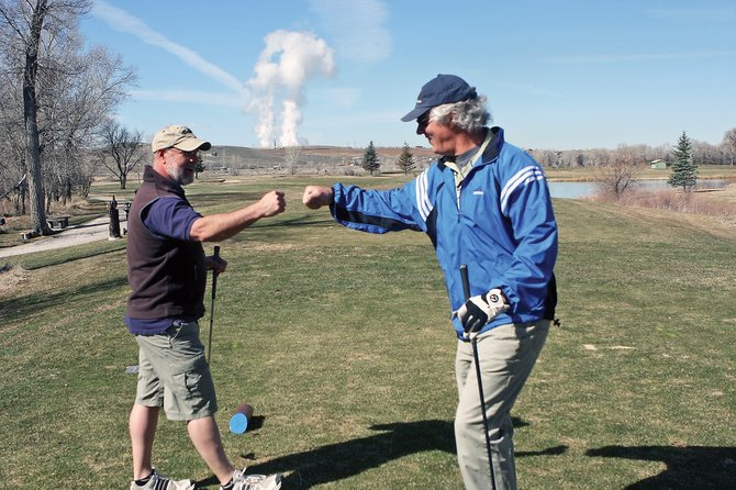 Kevin Rusk, left, pounds fists with Danny Thompson after both hit agreeable tee shots on the 11th hole Wednesday at Yampa Valley Golf Course. The course opened Saturday and has had a steady flow of golfers hitting the links.
