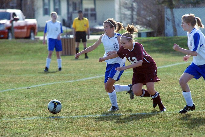 Moffat County's Kelly Ciesco, left, battles with a Palisade defender for the ball Thursday at Woodbury Sports Complex. The MCHS girls varsity soccer team fell, 3-1, to Palisade.